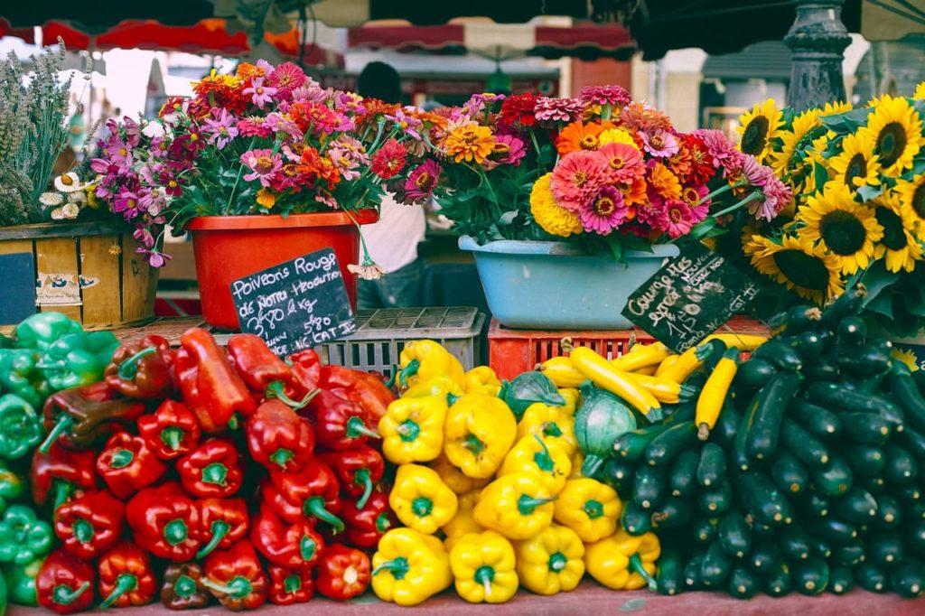 Photo d'un étalage de produits (légumes, fleurs ...) dans un commerce de proximité.